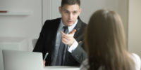 Two business people having a dialogue between, intended to reach a beneficial outcome man from human resource management interviewing a lady boss scolding his worker. Rear view at a woman. Business concept photo
