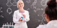 Young blond smiling teacher of chemistry holding tube with blue liquid substance while standing by blackboard with chemical formula